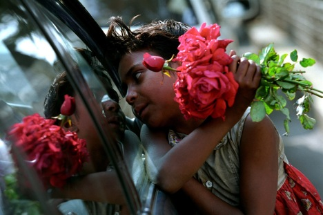 A girl is selling flower to the commuters of cars and buses plying on the road. Dhaka 2005
